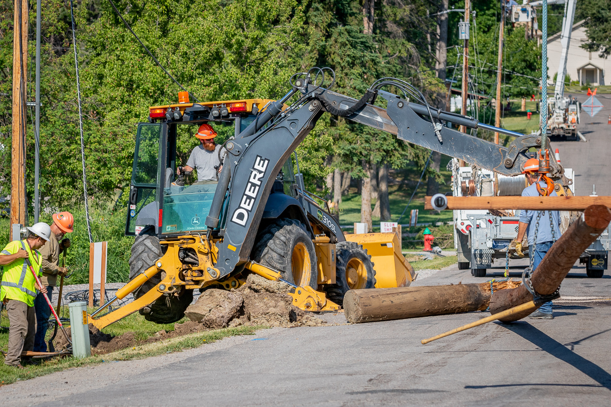 FEC crews use backhoe to remove the broken stump of a damaged power pole.